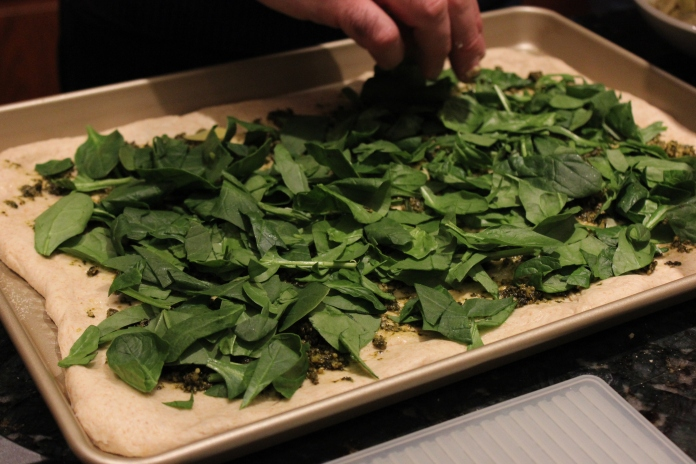 Adding the fresh spinach to the pizza dough